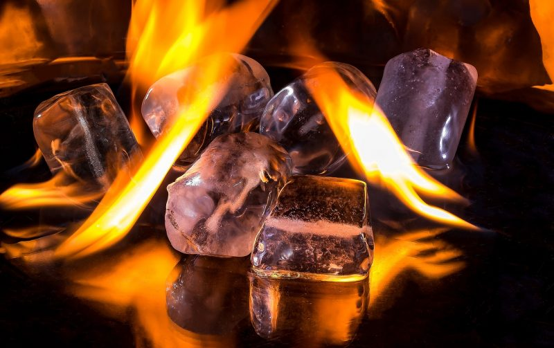 An image of flames melting ice cubes