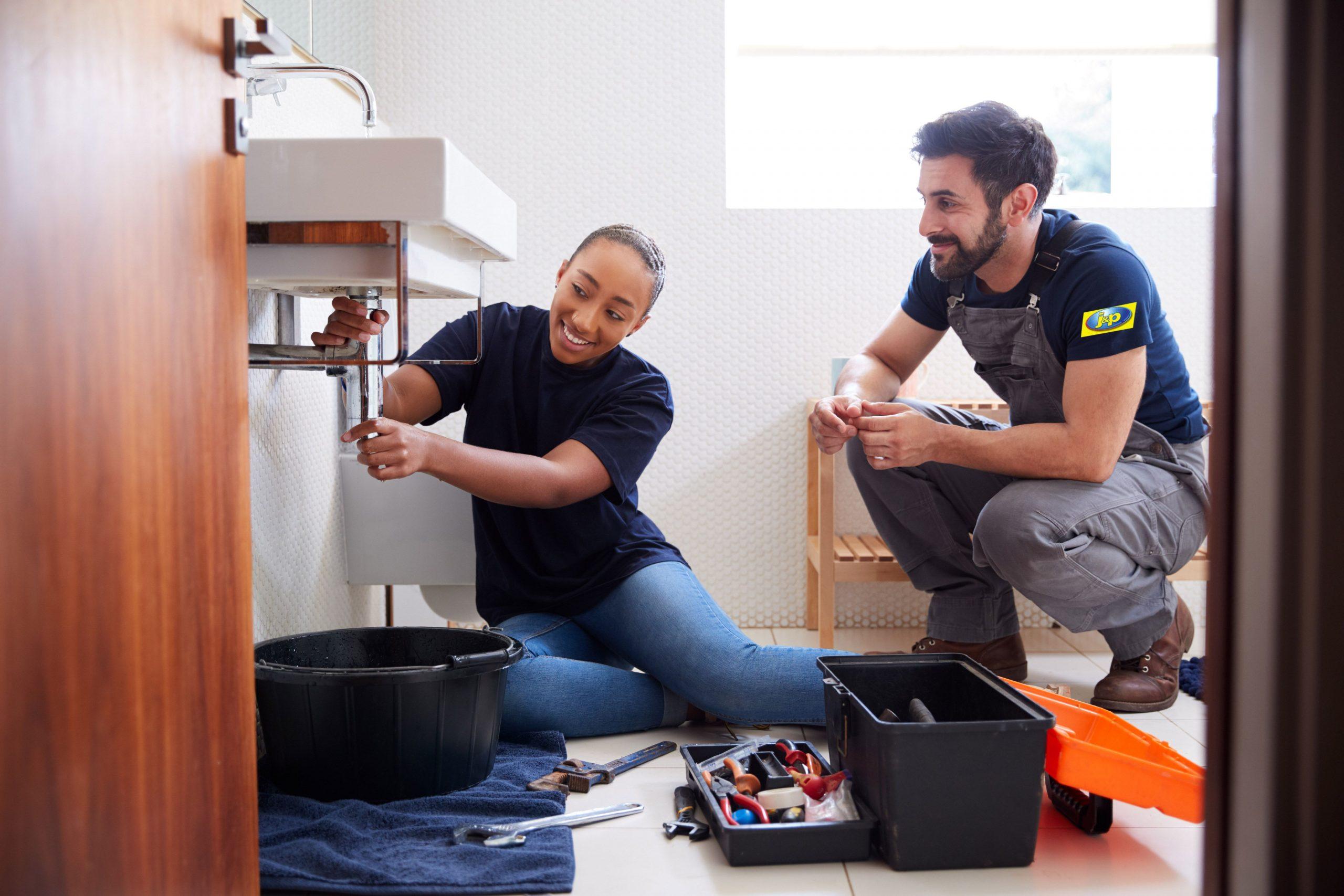 Male Plumber Teaching Female Apprentice To Fix Leaking Sink In Home Bathroom